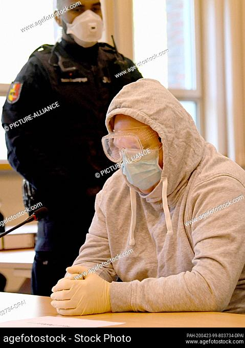 23 April 2020, Schleswig-Holstein, Schleswig: The 47-year-old defendant (r) sits in the courtroom with protective goggles and a face mask at the start of the...