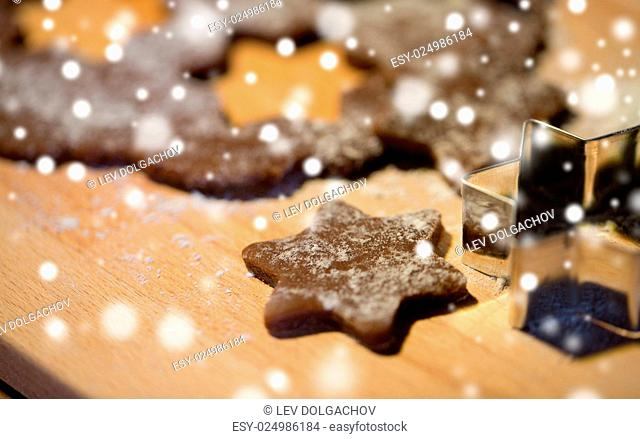 baking, cooking, christmas and food concept - close up of gingerbread dough, molds and flour on wooden cutting board from top
