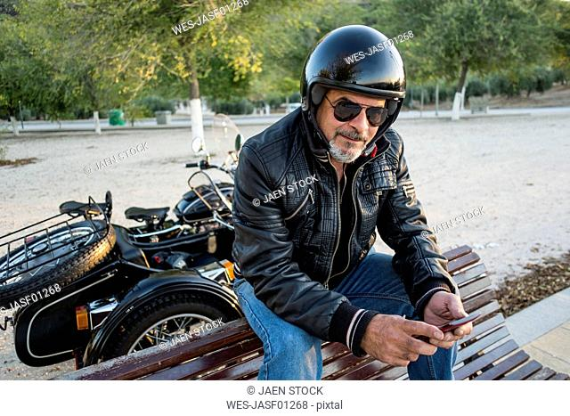 Portrait of biker wearing helmet and sunglasses sitting on backrest of a bench with smartphone