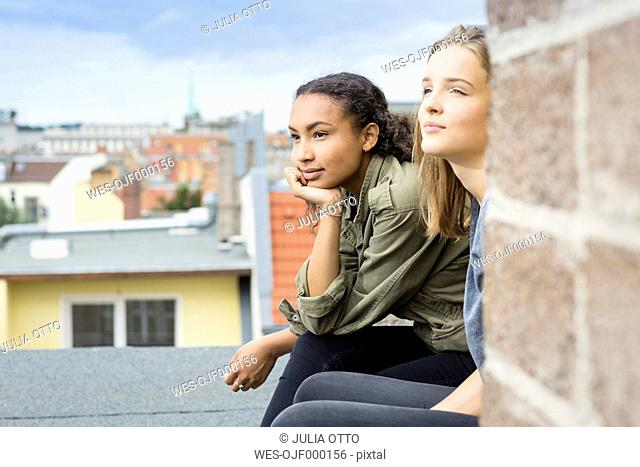 Two teenage girls sitting on roof top looking at distance