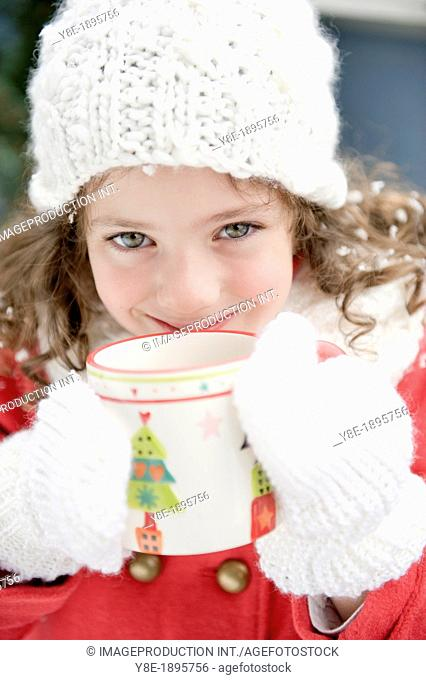 Portrait of girl (4-5) having hot drink in wintertime