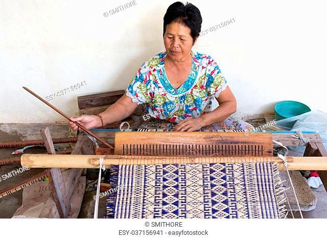 Thai woman weaving traditional straw mat using Cyperus alternifolius stems, Khon Kaen, Thailand