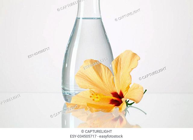 The vase with clean water and hibiskus flower on a glass table