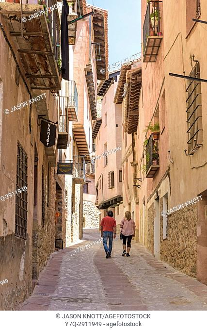 A couple walk through the narrow medieval streets with balconied houses wind through the Medieval Town of Albarracin, Teruel, Aragon, Spain