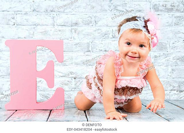 Beautiful and cute girl in pink dress with the letter E. Emotional girl