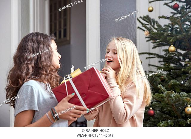 Girl handing over Christmas present to friend