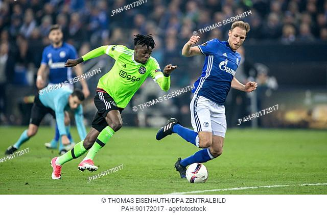 Schalke's Benedikt Hoewedes (R) against Amsterdam's Bertrand Traore during the UEFA Europe League quarter-final 2nd leg soccer match between FC Schalke 04 and...