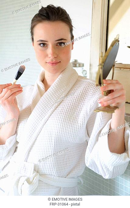 Young woman applying blush in bathroom