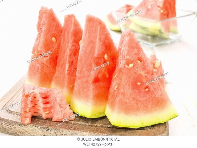 juicy watermelon slices on white wooden base