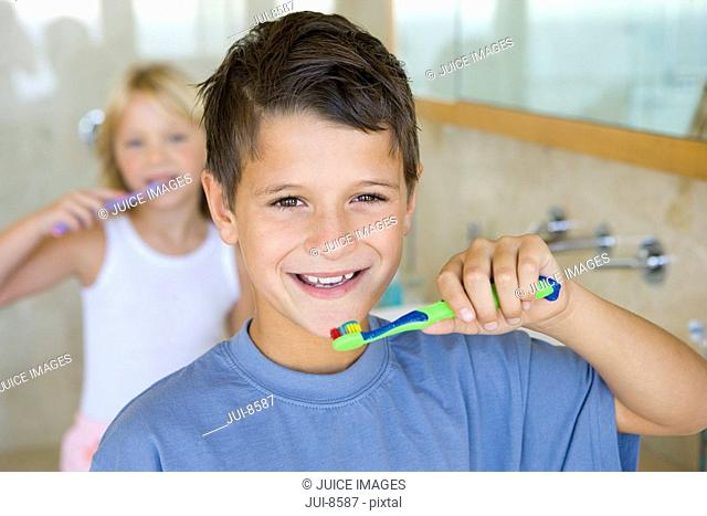 Boy and girl 6-8 brushing their teeth in bathroom, smiling, portrait