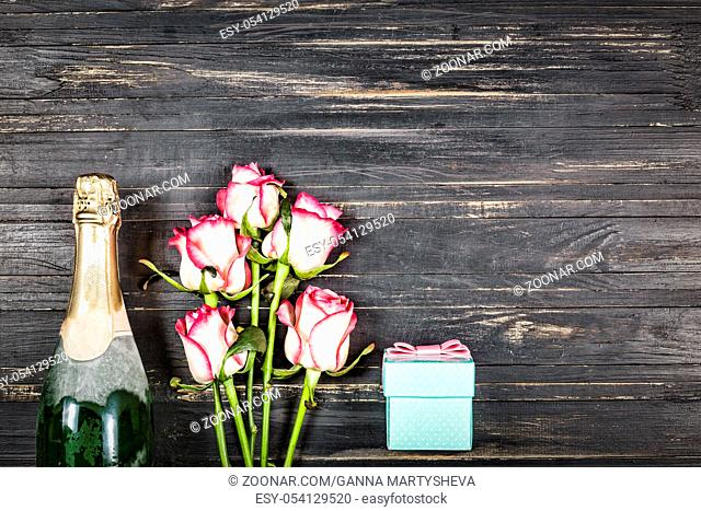 Concept Valentine's Day, Women's day, Mother's day, wedding day, birthday. Champagne, roses and gift box, top view, Copy spac