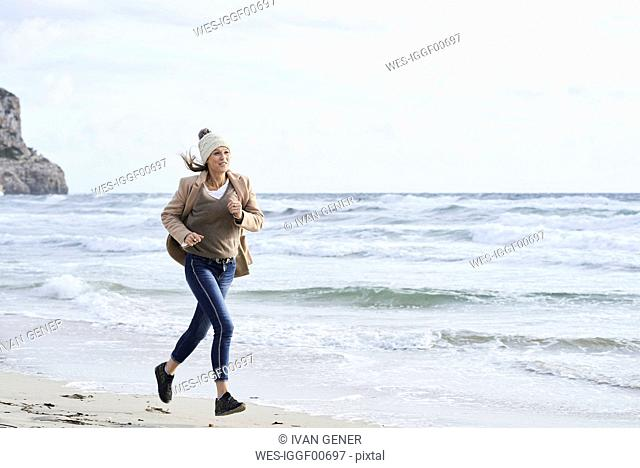 Spain, Menorca, senior woman jogging on the beach in winter