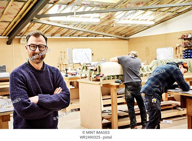 A furniture workshop making bespoke contemporary furniture pieces using traditional skills in modern design. Two people working and a man standing with arms...