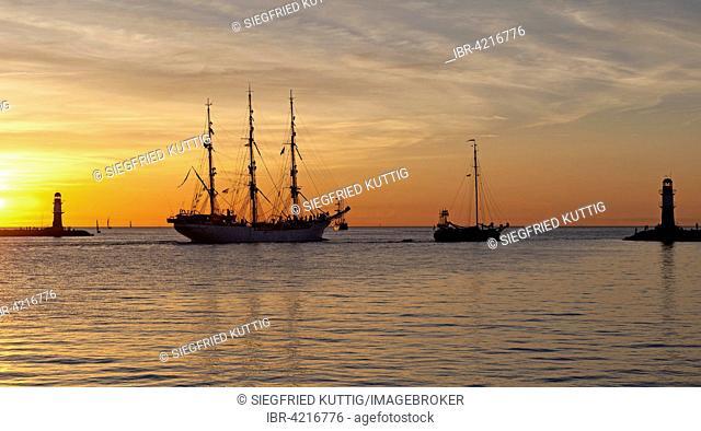 Sunset at harbor entrance, backlit sailboats, Hanse-Sail, Rostock, Mecklenburg-Western Pomerania, Germany