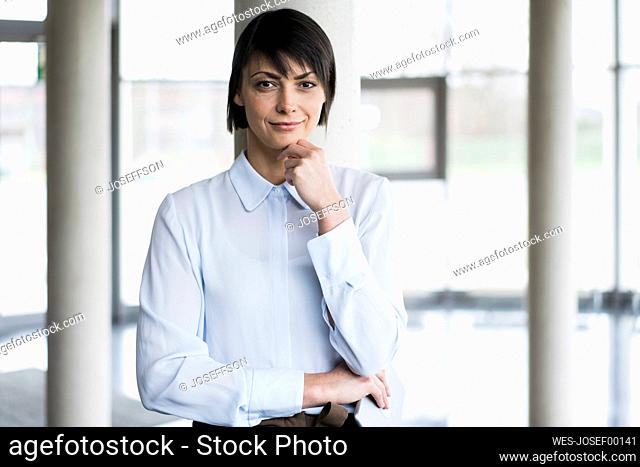 Serene businesswoman standing in bright office building