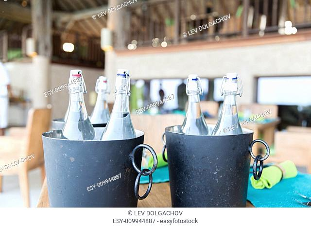 drinks, thirst, refreshment and summer resort concept - bottles of water in ice bucket at hotel restaurant