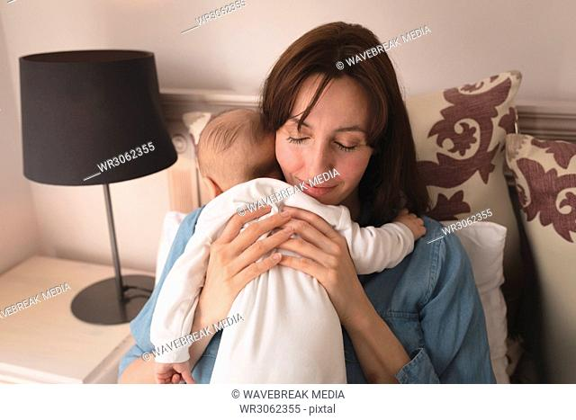 Young mom holding and hugging her baby