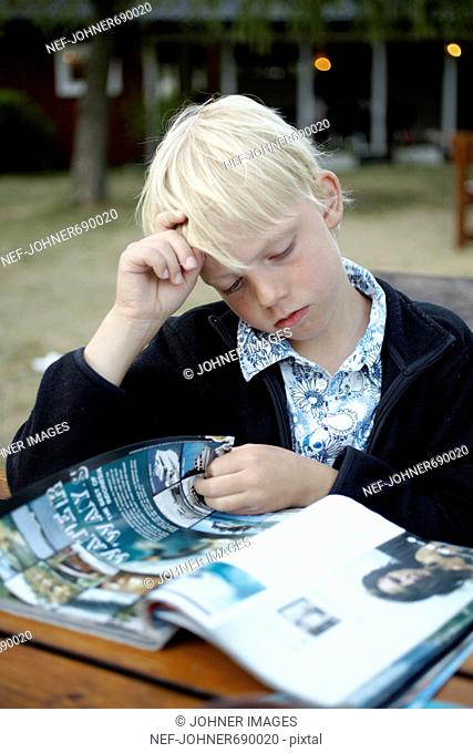 Scandinavian boy reading a magazine, Sweden