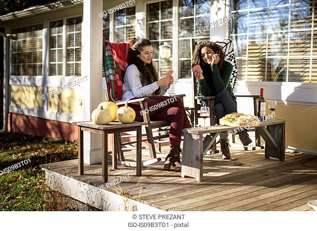 Two young female friends playing card game on patio