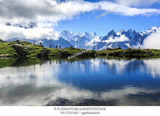 Low clouds and mist around Grandes Jorasses while hikers proceed on Lac De Cheserys Haute Savoie France Europe