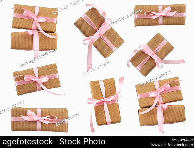 set of rectangular boxes wrapped in brown kraft paper and tied with a pink ribbon, gifts are isolated on a white background, element for a designer