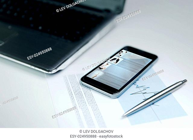 business, technology, social media and network concept - close up of smartphone with web page on screen, laptop computer and chart with pen on office table