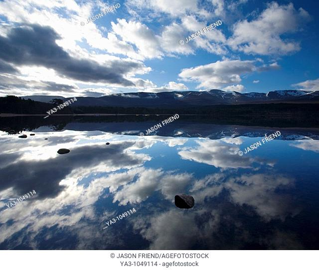 Scotland, Scottish Highlands, Cairngorms National Park  Dramatic clouds and Cairngorm mountains reflected upon the still face of Loch Morlich