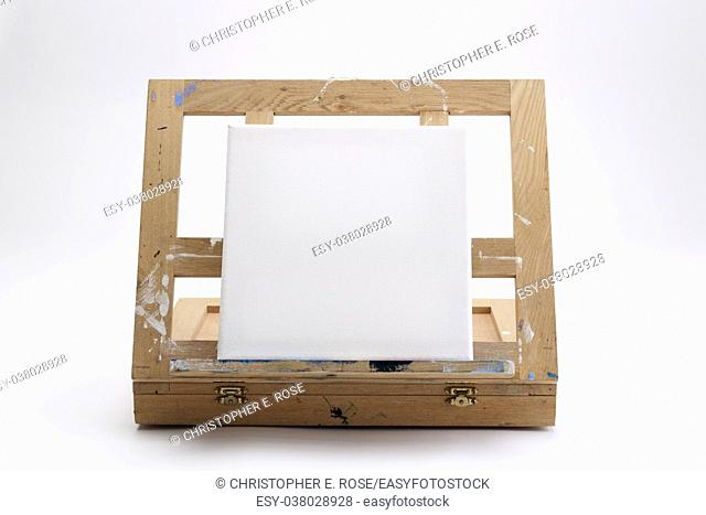 A well used artist's portable easel and case on white seamless with a square blank canvas waiting for an artwork to start