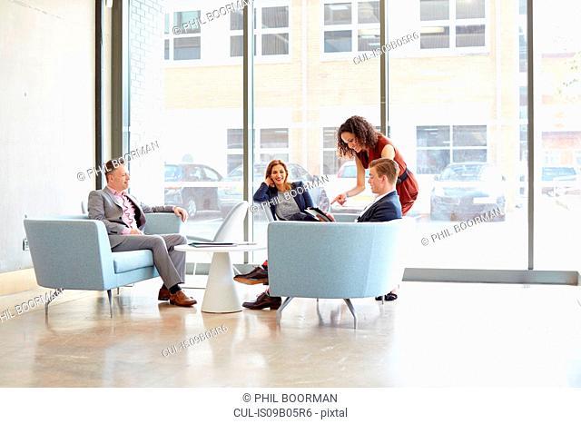 Businesswomen and men having meeting on office sofas