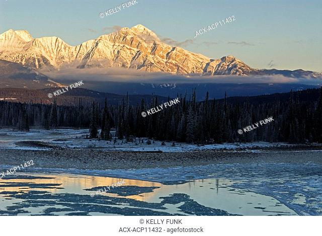 Pyramid Mountain sits in the sun's morning glow while early winter ice flows down the Athabasca river near Jasper, Alberta, Canada