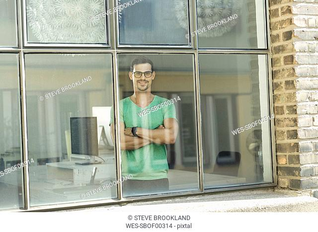 Young professional standing at the window