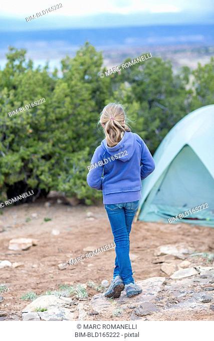 Caucasian girl standing at campsite in desert