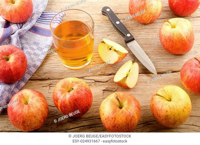 fresh apple juice and apples on rustic wooden table