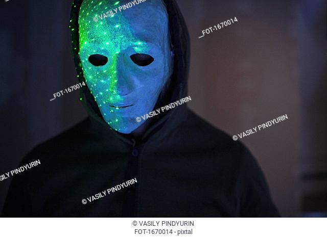 Close-up of man wearing mask with green lights against wall