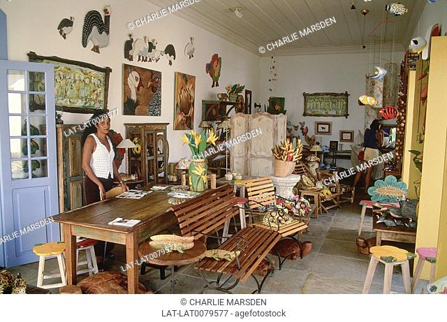 Interior of craft shop. Goods displayed. Woman standing. Bright coloured flowers