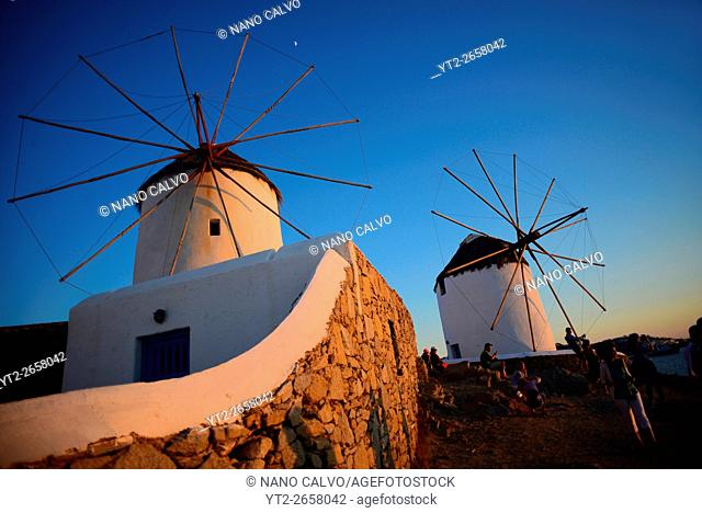 People enjoying sunset from traditional windmills (Kato Milli) in Mykonos town, Greece