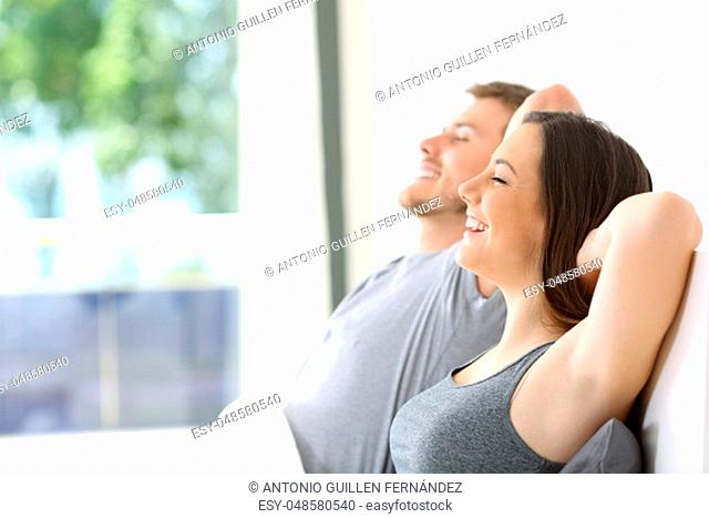Side view of a happy couple relaxing sitting on a bed of an hotel room or home