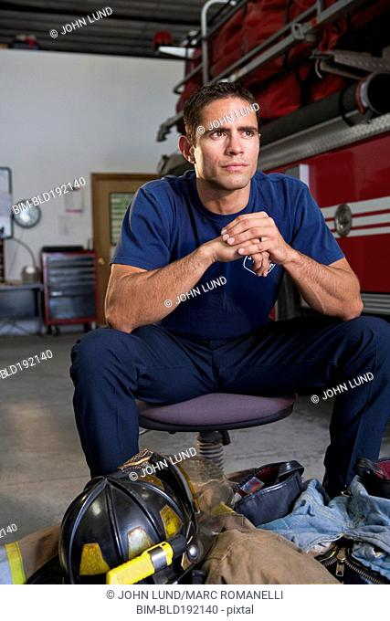 Hispanic fireman sitting with gear at feet