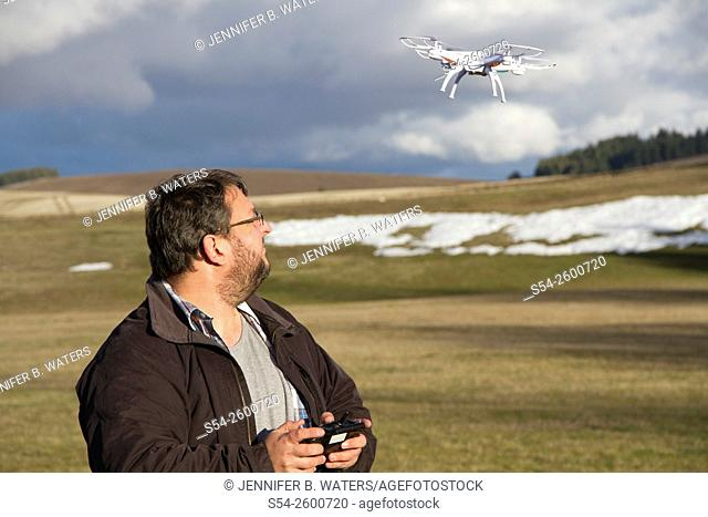 A man flying a small drone outdoors in Spokane county, USA