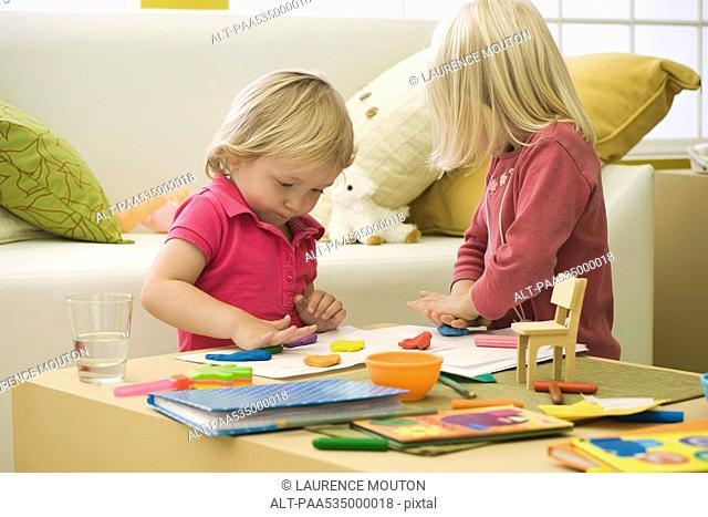 Little girls playing with clay on coffee table