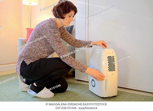 Woman with Portable dehumidifier colect water