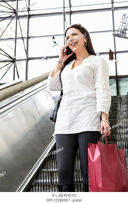 Business woman talking on her smart phone on an escalator after taking a shopping break during her work day; Edmonton, Alberta, Canada