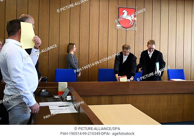 14 May 2019, Lower Saxony, Verden: When the defendant enters the court, he holds a sheet of paper in front of his face next to his lawyer, Michael Nagel