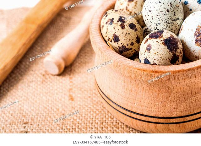 raw quail eggs in a wooden bowl on a burlap background