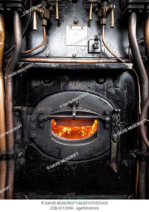 Burning coal fuel in the boiler of a vintage steam engine locomotive, North Yorkshire Moors Railway, on the North Yorkshire Moors, Yorkshire, UK