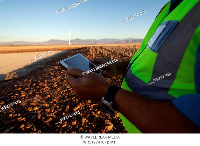 Engineer using a tablet at wind farm