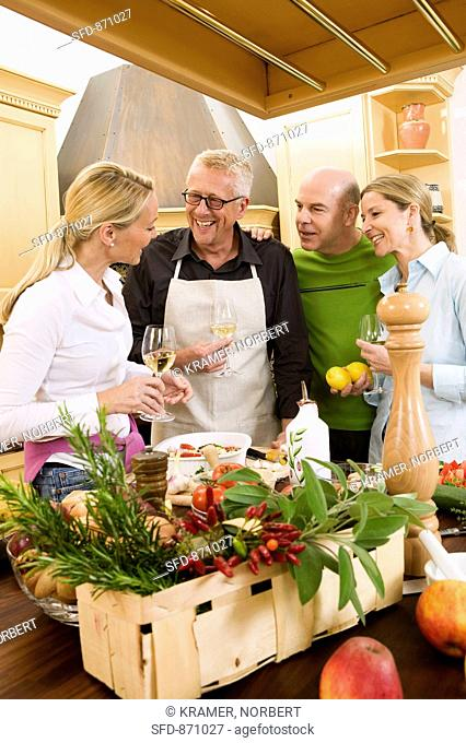 Two couples chatting whilst preparing food