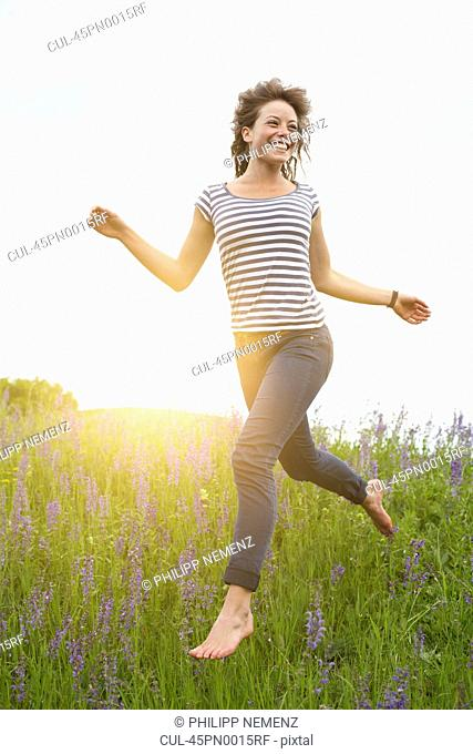 Woman leaping in tall grass