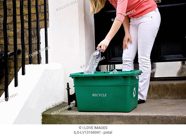 A young woman putting a plastic bottle in a recycling box