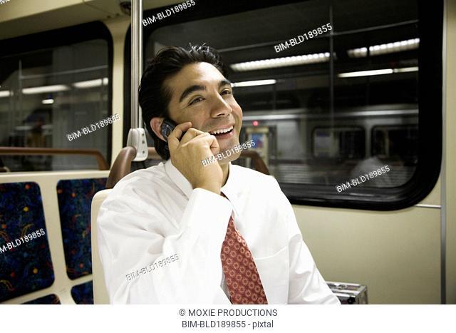 Hispanic businessman talking on cell phone on subway